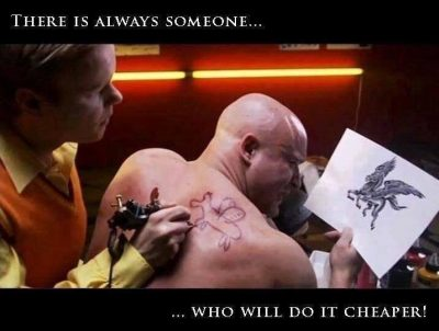 A tattoo artist putting a childish looking tattoo of a dragon on a man's back that is nothing like the picture he is holding in his hand.
